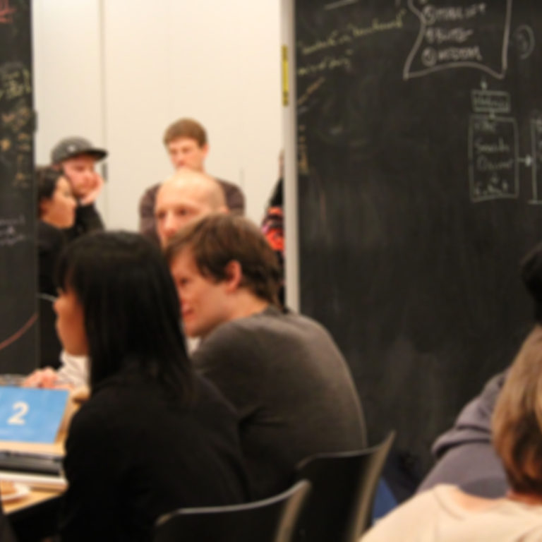 A number of people sit around tables in the foreground talking with eachother. In the background people stand next to two blackboards watching over the discussions happening.