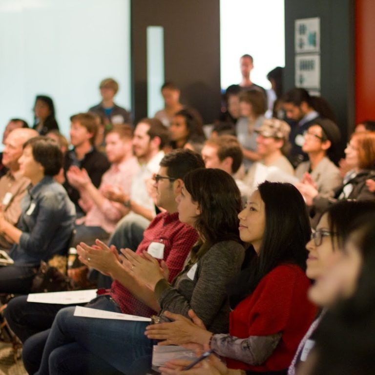 Two lines full of people sitting on chairs facing towards the front of a large room presumably listening to someone speak